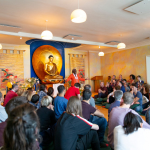 Suryagupta (chair of the London Buddhist Centre) in a packed shrine room during Buddha day. Photo: Sam Roberts / Louise Hall