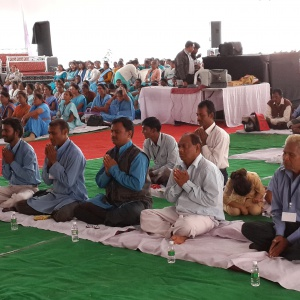 Men are sitting in a row for Mitra ceremony.